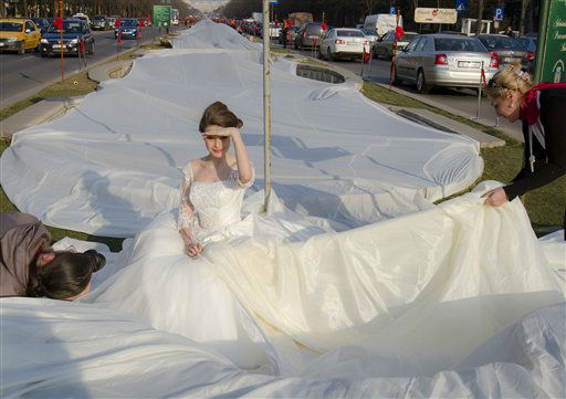 Emma Dumitrescu, 17-years old, a model, poses to show the world&#39;s longest wedding dress train during a Guinness World Record attempt in Bucharest, Romania, Tuesday, March 20, 1012.  Romania has set the world record for the world&#39;s longest bridal train.  The nearly 3-kilometer &#40;1.86-mile&#41; long ivory train, which took 100 days to stitch, was showcased dramatically on Tuesday on the boulevard leading up to the giant palace built by late dictator Nicolae Ceausescu, not pictured.  The previous record was 2.488 Km. &#40;AP Photo&#47;Vadim Ghirda&#41; <span class=meta>(AP Photo&#47; Vadim Ghirda)</span>
