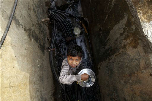 A young Indian boy holds a pot after collecting water from a broken pipe in a slum on the outskirts of Mumbai, India, Thursday, March 22, 2012. The U.N. estimates that more than one in six people worldwide do not have access to 20-50 liters &#40;5-13 gallons&#41; of safe freshwater a day to ensure their basic needs for drinking, cooking and cleaning. &#40;AP Photo&#47;Rafiq Maqbool&#41; <span class=meta>(AP Photo&#47; Rafiq Maqbool)</span>