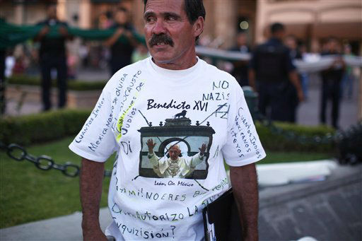 Fidencio Moreno wears a T-shirt protesting the upcoming visit of Pope Benedict XVI, which he says is being used for political purposes, in the main square in Leon, Mexico, Thursday March 22, 2012.  Pope Benedict XVI will arrive in Mexico Friday, a decade after his predecessor&#39;s last visit, to a very different country and a church that has suffered debilitating setbacks amidst sex abuse scandals and a lower percentage of Mexicans who call themselves Catholic today, compared to a decade ago. &#40;AP Photo&#47;Alexandre Meneghini&#41; <span class=meta>(AP Photo&#47; Alexandre Meneghini)</span>