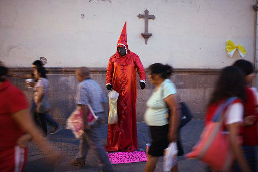 People walk past a street artist dressed as a magician performing for money by a church in the main square in Leon, Mexico, Thursday March 22, 2012. Pope Benedict XVI will arrive in Mexico Friday, a decade after his predecessor&#39;s last visit, to a very different country and a church that has suffered debilitating setbacks amidst sex abuse scandals and a lower percentage of Mexicans who call themselves Catholic today, compared to a decade ago. &#40;AP Photo&#47;Alexandre Meneghini&#41; <span class=meta>(AP Photo&#47; Alexandre Meneghini)</span>