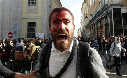 A young man bleeding from his head shouts towards a line of policemen following clashes between the police and protestors during a demonstration in Lisbon, Thursday, March 22, 2012. On Thursday Portugal&#39;s largest trade union called a general strike to protest austerity measures and labor reforms. &#40;AP Photo&#47;Francisco Seco&#41; <span class=meta>(AP Photo&#47; Francisco seco)</span>