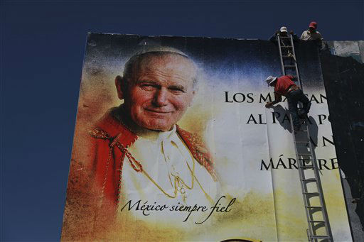 Workers paste an image of the late Pope John Paul II to a giant billboard in Silao, Mexico, Thursday March 22, 2012. It&#39;s been a decade since the former pope visited Mexico; his fifth and final trip to the country. His successor, Pope Benedict XVI, arrives Friday, to a very different country and welcomed by a church that has suffered debilitating setbacks amidst sex abuse scandals and a lower percentage of Mexicans who call themselves Catholic today compared to a decade ago. &#40;AP Photo&#47;Dario Lopez-Mills&#41; <span class=meta>(AP Photo&#47; Dario Lopez-Mills)</span>