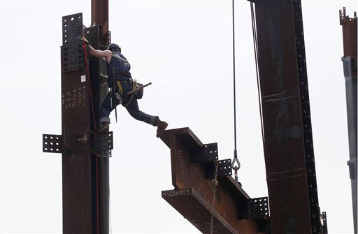An ironworker holds on to a column as he reaches out with his foot to guide a beam into place above the 93rd floor of One World Trade Center, Friday, March 23, 2012 in New York, The tower, formerly known as the Freedom Tower, will reach 104 floors and is scheduled for completion in 2013. &#40;AP Photo&#47;Mark Lennihan&#41; <span class=meta>(AP Photo&#47; Mark Lennihan)</span>