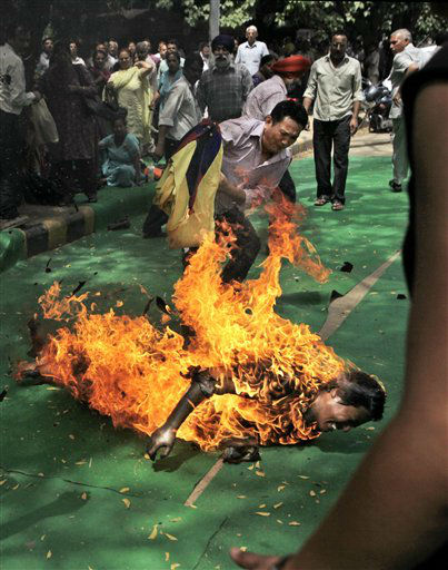 A Tibetan protester tries to extinguish the fire with a Tibetan flag as a man, identified as Jampa Yeshi, is engulfed in flames after self-immolating at a protest in New Delhi, India, ahead of Chinese President Hu Jintao&#39;s visit to the country Monday, March 26, 2012. The Tibetan activist lit himself on fire at the gathering and was rushed to hospital with unknown injuries, reports said. &#40;AP Photo&#47;Manish Swarup&#41; <span class=meta>(AP Photo&#47; Manish Swarup)</span>