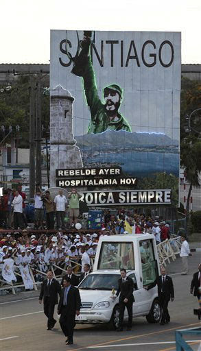 Backdropped by a billboard showing Cuba&#39;s leader Fidel Castro, Pope Benedict XVI arrives aboard the popemobile to Revolution Square to celebrate a Mass in Santiago de Cuba, Cuba, Monday, March 26, 2012. Pope Benedict XVI is in Cuba for a three-day visit.&#40;AP Photo&#47;Gregorio Borgia&#41; <span class=meta>(AP Photo&#47; Gregorio Borgia)</span>