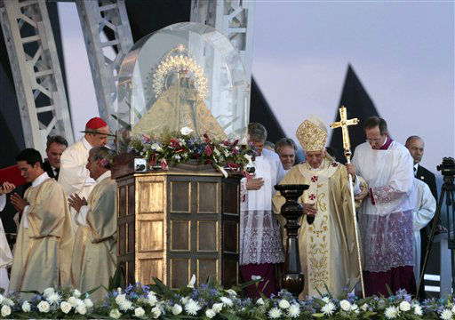 Pope Benedict XVI wlks by the Virgen of the Chariry of Cobre before conducting a Mass at Revolution Square in Santiago de Cuba, Cuba, Monday, March 26, 2012. Pope Benedict XVI is in Cuba for a three-day visit. &#40;AP Photo&#47;Esteban Felix&#41; <span class=meta>(AP Photo&#47; Esteban Felix)</span>