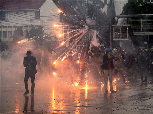 A tear gas canister fired by Indonesian police officers explodes in the air during a protest against the government&#39;s plan to raise fuel prices in Jakarta, Indonesia, Tuesday, March 27, 2012. The Indonesian government plans to raise fuel prices by about 33 percent next month to avoid a budget deficit due to expensive fuel subsidies. &#40;AP Photo&#47;Dita Alangkara&#41; <span class=meta>(AP Photo&#47; Dita Alangkara)</span>
