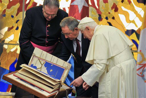 Pope Benedict XVI, right, presents a replica of Tolomeus Geography book to Cuba&#39;s President Raul Castro, center, during a meeting in Havana, Cuba, Tuesday, March 27, 2012. The meeting took place behind closed doors on the pontiff&#39;s second day on the island. &#40;AP Photo&#47;Adalberto Roque, Pool&#41; <span class=meta>(AP Photo&#47; Adalberto Roque)</span>