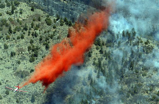 A trail of slurry is deposited by a bomber during a run over a smoldering ridge in the Lower North Fork Wildfire burning in the foothills community of Conifer, Colo., southwest of Denver on Tuesday, March 27, 2012. Firefighters are now able to actively battle the blaze on the ground that started on Monday and has already destroyed at least 16 homes in the rugged terrain. &#40;AP Photo&#47;David Zalubowski&#41; <span class=meta>(AP Photo&#47; David Zalubowski)</span>