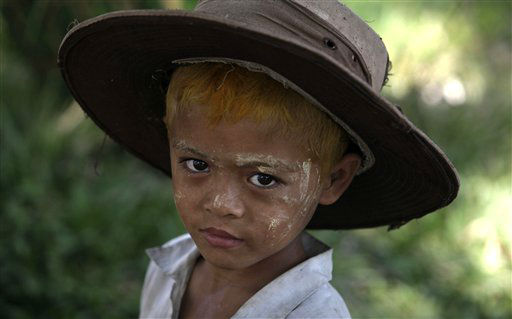 A Myanmar boy wears an over-sized hat in the village of Wah Thin Kha from where pro-democracy leader Aung San Suu Kyi is standing for by-elections in Myanmar, Thursday, March 29, 2012. (AP Photo/Altaf Qadri)