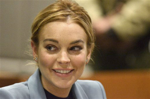 Lindsay Lohan smiles in court during a progress report on her probation for theft charges at Los Angeles Superior Court Thursday, March 29, 2012. Lohan will update a judge on her progress on strict probation requirements that have had her doing cleanup duty at the county morgue and attending regular psychotherapy sessions since late last year. Superior Court Judge Stephanie Sautner has said she will end Lohan&#39;s probation on a 2007 drunken driving case on Thursday if she completes the requirements. &#40;AP Photo&#47;Joe Klamar, Pool&#41; <span class=meta>(AP Photo&#47; Joe Klamar)</span>