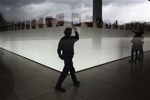 Dark clouds reflecting in the windows of the Neue Nationalgalerie museum as a boy takes pictures of paintings by artist Gerhard Richter in Berlin, Friday, March 30, 2012. (AP Photo/Markus Schreiber)
