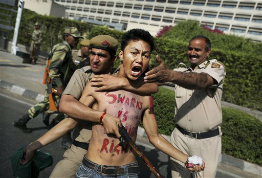 Indian police detain a Tibetan protester during a demonstration against the visit of Chinese President Hu Jintao outside his hotel in New Delhi, India, Friday, March 30, 2012. The Chinese leader left India Friday after attending the BRICS Summit. (AP Photo/Kevin Frayer)