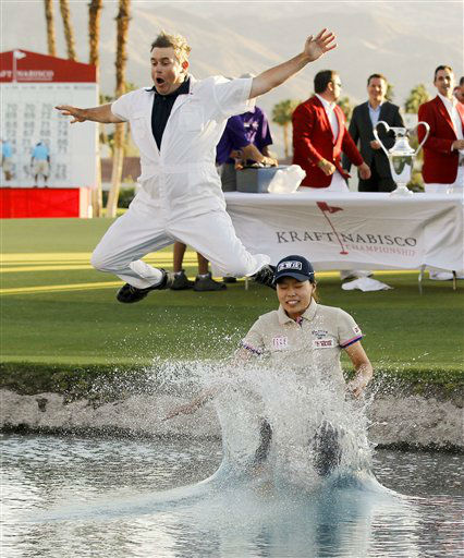 Sun Young Yoo, of South Korea, jumps into the water with her caddie, Adam Woodward, after her playoff win during the final round of the LPGA Kraft Nabisco Championship golf tournament in Rancho Mirage, Calif., Sunday, April 1, 2012. &#40;AP Photo&#47;Chris Carlson&#41; <span class=meta>(AP Photo&#47; Chris Carlson)</span>