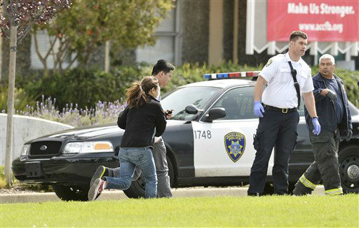 An unidentified man and woman run past an Oakland Police car outside of Oikos University in Oakland, Calif., Monday, April 2, 2012. A suspect was detained Monday in a shooting attack at a California Christian university that sources said has left at least five people dead. &#40;AP Photo&#47;Noah Berger&#41; <span class=meta>(AP Photo&#47; Noah Berger)</span>