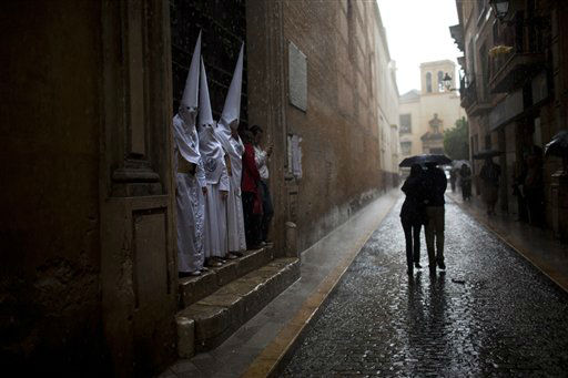 Penitents from &#34;La Candelaria&#34; brotherhood shelter from rain as a couple walk along the street during a storm in Seville, Southern Spain, Tuesday, April 3, 2012. Most of the processions were canceled in Seville due to bad weather during the Easter Holy Week. &#40;AP Photo&#47;Emilio Morenatti&#41; <span class=meta>(AP Photo&#47; Emilio Morenatti)</span>