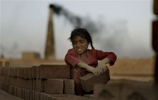 Pakistani girl Naginah Sadiq, 5, arranges bricks where she and her family are working in a brick factory on the outskirts of Islamabad, Pakistan, Tuesday, April 3, 2012. Naginah earns 250 Rupees &#40;&#36;2 .77 cents&#41; per day according to her father.  &#40;AP Photo&#47;Muhammed Muheisen&#41; <span class=meta>(AP Photo&#47; Muhammed Muheisen)</span>