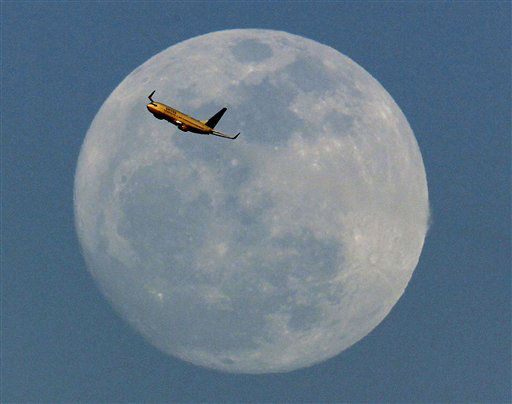A United Airlines jet taking off from Newark Liberty International Airport flies across the moon seen from Eagle Rock Reservation in West Orange, N.J., Thursday, April 5, 2012. &#40;AP Photo&#47;Julio Cortez&#41; <span class=meta>(AP Photo&#47; Julio Cortez)</span>