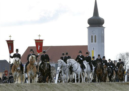 Men of the Sorbian community ride on decorated horses during the traditional Easter procession in Ralbitz, 70km &#40;45miles&#41; east of Dresden, Germany, Sunday, April 8, 2012. Sorbian men wearing black coats and top hats, sing holy songs on horseback and preach the message of Jesus&#39; resurrection. The Sorbs are a Slavic, Catholic minority group in eastern Germany. &#40;AP Photo&#47;Gero Breloer&#41; <span class=meta>(AP Photo&#47; Gero Breloer)</span>