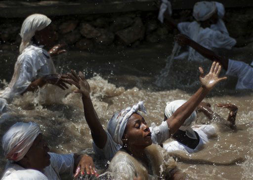 Voodoo believers swim in a sacred pool during a Voodoo ceremony in Souvenance, Haiti, Sunday, April 8, 2012. Hundreds of voodoo followers travel to Souvenance over Easter weekend to show their devotion to the spirits. Voodoo was brought to Haiti by slaves from West Africa and is one of Haiti&#39;s three recognized religions. &#40;AP Photo&#47;Ramon Espinosa&#41; <span class=meta>(AP Photo&#47; Ramon Espinosa)</span>