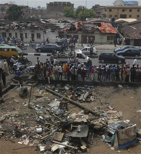 People gather at the site of a suicide car bomb explosion with the wreckage of a road side shop, foreground, and damaged houses, following a suicide car bomb explosion in Kaduna, Nigeria, Tuesday, April 10, 2012.  The death toll is still rising from the Sunday April 8, suicide car bomb, which has killed at least 41-people in Kaduna over the weekend.&#40;AP Photos&#47;Sunday Alamba&#41; <span class=meta>(AP Photo&#47; Sunday Alamba)</span>