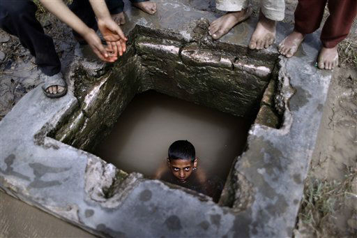 A Pakistani boy swims in a water reservoir to cool off as the temperature rises, while others wait their turn, next to a slum area on the outskirts of Islamabad, Pakistan, Tuesday, April 10, 2012. &#40;AP Photo&#47;Muhammed Muheisen&#41; <span class=meta>(AP Photo&#47; Muhammed Muheisen)</span>