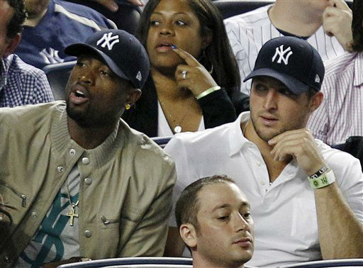 Miami Heat&#39;s Dwayne Wade, left, sits beside New York Jets quarterback Tim Tebow during the New York Yankees baseball game against the Los Angeles Angels at Yankee Stadium in New York, Sunday, April 15, 2012. &#40;AP Photo&#47;Kathy Willens&#41; <span class=meta>(AP Photo&#47; Kathy Willens)</span>
