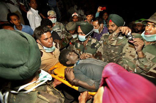 "<div class=""meta image-caption""><div class=""origin-logo origin-image ""><span></span></div><span class=""caption-text"">Rescue workers carry Indian survivor Sandeep out from the rubble of a factory that collapsed in Jalandhar, India, Wednesday, April 18, 2012. Rescue work continues at the site of a three-story blanket factory that collapsed in northern India close to midnight Sunday, killing at least five people. (AP Photo/Channi Anand)</span></div>"