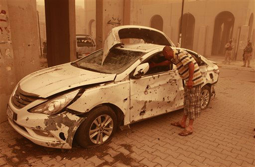Mahmoud Ali inspects his destroyed car during a sandstorm after a car bomb explosion in Haifa Street, Baghdad, Iraq, Thursday, April 19, 2012. A wave of morning bombings across several cities on Thursday, killing and injuring dozens of Iraqis, police said, shattering weeks of calm in a reminder of the nation&#39;s continued insurgency. &#40;AP Photo&#47;Karim Kadim&#41; <span class=meta>(AP Photo&#47; Karim Kadim)</span>