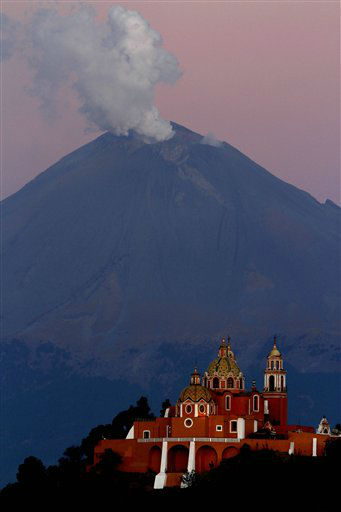 A plume of ash and steam rise from the Popocatepetl volcano overshadowing the Catholic church Nuestra Se&#241;ora de los Remedios or Our Lady of Remedies in Cholula, in the Mexican state of Puebla, Sunday, April 22, 2012. Popo, as the volcano is commonly known, has put out small eruptions of ash almost daily since a round of eruptive activity began in 1994. A week ago, the eruptions started growing larger. Authorities prepared evacuation routes, ambulances and shelters in the event of a bigger explosion.  &#40;AP Photo&#47;Marco Ugarte&#41; <span class=meta>(AP Photo&#47; Marco Ugarte)</span>