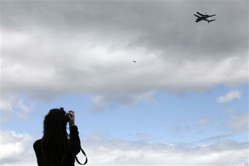 A woman takes a photograph as the Space shuttle Enterprise, riding on the back of the NASA 747 Shuttle Carrier Aircraft, flies past in Jersey City, N.J., Friday, April 27, 2012. Enterprise is eventually going to make its new home in New York City at the Intrepid Sea, Air and Space Museum. &#40;AP Photo&#47;Mel Evans&#41; <span class=meta>(AP Photo&#47; Mel Evans)</span>