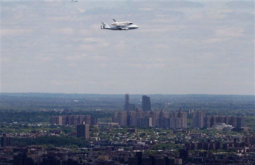 Space shuttle Enterprise, riding on the back of the NASA 747 Shuttle Carrier Aircraft, flies over the Queens borough of New York on its way to Kennedy Airport, in New York, Friday, April 27, 2012. Enterprise is eventually going to make its new home in New York City at the Intrepid Sea, Air and Space Museum. (AP Photo/Richard Drew)