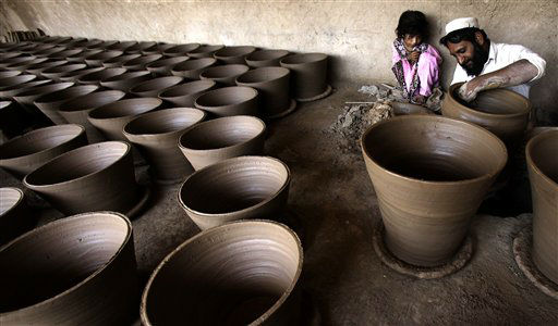 A Pakistani girl looks as her father Abdul Rehman makes pots in Peshawar, Pakistan, Monday, April 30, 2012. &#40;AP Photo&#47;Mohammad Sajjad&#41; <span class=meta>(AP Photo&#47; Mohammad Sajjad)</span>