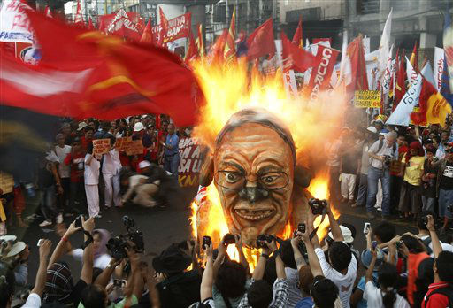 Protesters burn an effigy of Philippine President Benigno Aquino III during a rally near the Presidential Palace in Manila to celebrate international Labor Day known as May Day Tuesday May 1, 2012 in the Philippines. Thousands of workers marched under a brutal sun in Manila to demand a wage increase amid an onslaught of oil price increases, but the Philippine President rejected a &#36;3 daily pay hike which the workers have been demanding since 1999 and warned may worsen inflation, spark layoffs and turn away foreign investors. &#40;AP Photo&#47;Bullit Marquez&#41; <span class=meta>(AP Photo&#47; Bullit Marquez)</span>