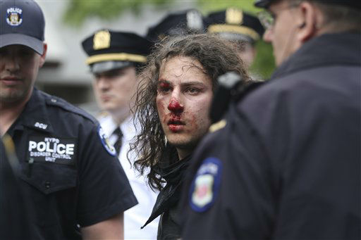 Police officers surround a bloodied demonstrator after his arrest during an un-permitted march,  Tuesday, May 1, 2012 in New York. Hundreds of activists with a variety of causes spread out over New York City Tuesday on International Workers Day, or May Day, with Occupy Wall Street members leading a charge against financial institutions. &#40;AP Photo&#47;Mary Altaffer&#41; <span class=meta>(AP Photo&#47; Mary Altaffer)</span>