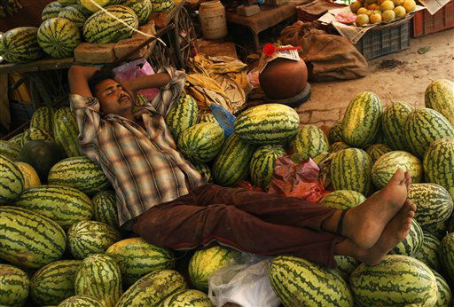An Indian watermelon vendor takes a nap on a hot summer afternoon in Allahabad, India, Wednesday, May 2, 2012.  &#40;AP Photo&#47;Rajesh Kumar Singh&#41; <span class=meta>(AP Photo&#47; Rajesh Kumar Singh)</span>