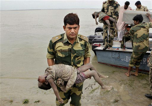 Paramilitary soldiers carry dead bodies of children, victims of a ferry capsize in the Brahmaputra River, at Buraburi village, about 350 kilometers &#40;215 miles&#41; west of the state capital Gauhati, India, Wednesday, May 2, 2012. Grieving relatives and survivors gathered on the banks of the turbulent river in northeast India for a second day Wednesday waiting for news of their loved ones missing since a heavily packed ferry capsized killing more than a 100 people and left more than 100 missing. &#40;AP Photo&#47;Anupam Nath&#41; <span class=meta>(AP Photo&#47; Anupam Nath)</span>