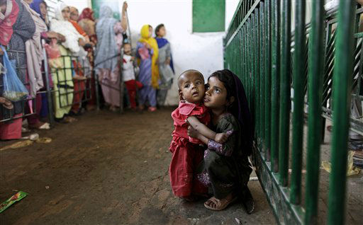 Pakistani Abla Zahir, 6, sits on the ground holding her brother Yaseen, 1, while waiting to receive a ration of rice during a donated food distribution at the Beri Iman, a shrine of famous Sufi Saint Beri Imam, in Islamabad, Pakistan, Friday, May 4, 2012. &#40;AP Photo&#47;Muhammed Muheisen&#41; <span class=meta>(AP Photo&#47; Muhammed Muheisen)</span>