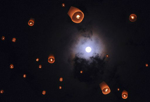 In this late Sunday, May 6, 2012 photo, lanterns release by Buddhist worshippers fly as full moon is seen in the background during a procession commemorating Waisak day which marks the birth, death and enlightenment of Buddha at the 9th century Borobudur temple in Magelang, Central Java, Indonesia. &#40;AP Photo&#47;Slamet Riyadi&#41; <span class=meta>(AP Photo&#47; Slamet Riyadi)</span>
