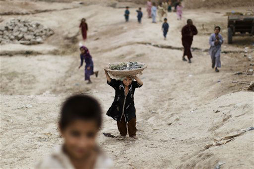 An Afghan refugee girl, center, returns home carrying a basket on her head in a slum area on the outskirts of Islamabad, Pakistan, Monday, May 7, 2012. &#40;AP Photo&#47;Muhammed Muheisen&#41; <span class=meta>(AP Photo&#47; Muhammed Muheisen)</span>