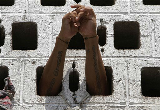 A prisoner rests his arms in the wall of his cell during a Mass for prisoners in the courtyard of La Esperanza penal center in San Salvador, El Salvador, Monday, May 7, 2012. The prisoners asked for Monsignor Fabio Colindres to hold a Mass for them at the prison.  &#40;AP Photo&#47;Luis Romero&#41; <span class=meta>(AP Photo&#47; Luis Romero)</span>