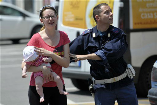 An Italian policeman helps a woman and her baby during an earth tremor in Mirandola, northern Italy, Tuesday, May 29, 2012. A magnitude 5.8 earthquake struck northern Italy on Tuesday, killing at least 10 people as factories, warehouses and a church collapsed in the same region still struggling to recover from another deadly tremor nine days ago. (AP Photo/Marco Vasini)