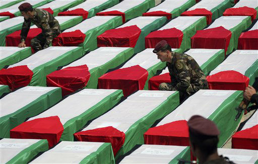 "<div class=""meta ""><span class=""caption-text "">Members of the Palestinian security forces arrange Palestinian flags on coffins containing the remains of bodies of 91 militants transferred from Israel to the Palestinian Authority, in the West Bank city of Ramallah, Thursday, May 31, 2012. Israel transferred the bodies in an effort to induce Palestinian President Mehmoud Abbas to renew negotiations. Palestinian officials said all were killed either while carrying out suicide bombings or other attacks on Israeli targets. (AP Photo/Mohammed Ballas) (AP Photo/ Mohammed Ballas)</span></div>"