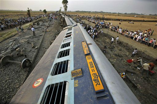 Officials and locals gather around the fallen compartments of Doon Express, a passenger train which derailed in Jaunpur, Uttar Pradesh state, India, Thursday, May 31, 2012. According to news reports at least five people were killed and about fifty others injured after the passenger train which was traveling from Howrah station, near Calcutta city, to Dehradun in the state of Uttarakhand derailed. (AP Photo/Rajesh Kumar Singh)