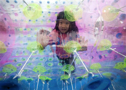 A child plays inside a balloon float on water at the Chaoyang park during International Children's Day in Beijing Friday, June 1, 2012. (AP Photo/Andy Wong)