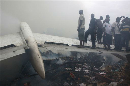 People stand on a wing of a wrecked passenger plane in Lagos, Nigeria, Sunday, June 3, 2012.  All 153 passengers on board the plane are dead, an aviation official says. The plane crashed in a densely populated neighborhood near the airport. A spokesman for Nigeria&#39;s national emergency management agency said there were likely more casualties on the ground, but the number was unknown. &#40;AP Photo&#47;Sunday Alamba&#41; <span class=meta>(AP Photo&#47; Sunday Alamba)</span>