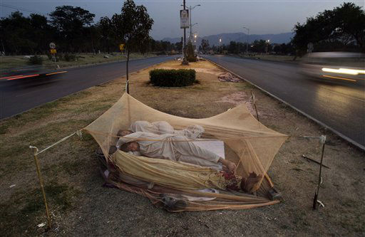 Vehicles move past Pakistani day laborers, sleeping under a mosquito net, in the middle of a street in Islamabad, Pakistan, early Monday, June 4, 2012. &#40;AP Photo&#47;Muhammed Muheisen&#41; <span class=meta>(AP Photo&#47; Muhammed Muheisen)</span>