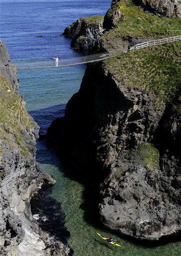 Denis Broderick carries the Olympic Torch over the Carrick-a-Rede rope bridge in county Antrim, Northern Ireland, Monday, June 4, 2012.  The Olympic Torch is continuing its relay journey around the country, and is scheduled to arrive at the opening ceremony of the London 2012 Olympic Games. &#40;AP Photo&#47;Peter Morrison&#41; <span class=meta>(AP Photo&#47; Peter Morrison)</span>