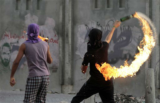 "<div class=""meta ""><span class=""caption-text "">Bahraini anti-government protesters, near a wall sprayed with images of jailed opposition political activists, throw petrol bombs toward riot police, unseen, Tuesday, June 5, 2012, in the western village of Malkiya, Bahrain. Clashes broke out after a march demanding democracy and that prisoners be freed. Also on Tuesday, a Bahraini defense lawyer says jailed activists challenging verdicts issued against them by a military-led tribunal recounted in court that they had been subjected to torture and beatings after their arrest. (AP Photo/Hasan Jamali) (AP Photo/ Hasan Jamali)</span></div>"