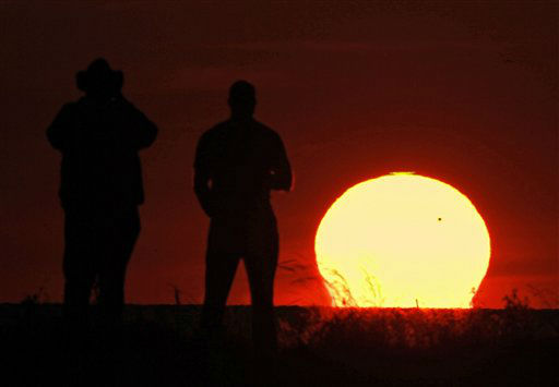 Spectators at Edgewater Park in Cleveland watch the sun set as the planet Venus crosses the upper right portion of the star, Tuesday, June 5, 2012. The next transit of Venus won&#39;t be for another 105 years. &#40;AP Photo&#47;Mark Duncan&#41; <span class=meta>(AP Photo&#47; Mark Duncan)</span>
